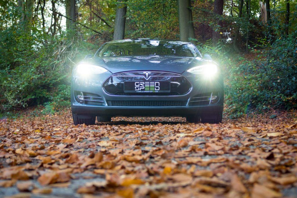 Tesla Model S85 grau metallic eingeschaltete Frontscheinwerfer Aachen Park Laub Herbst Straße Weg greenspeed emobility Deutschland gebraucht kaufen