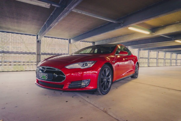 Tesla Model S85 rot multicoat Cyclone Felgen Aachen Deutschland urban Parkhaus Schrägansicht vorne Exterieur Karosserie ausgeschaltete Scheinwerfer emobility Gebrauchtwagen kaufen