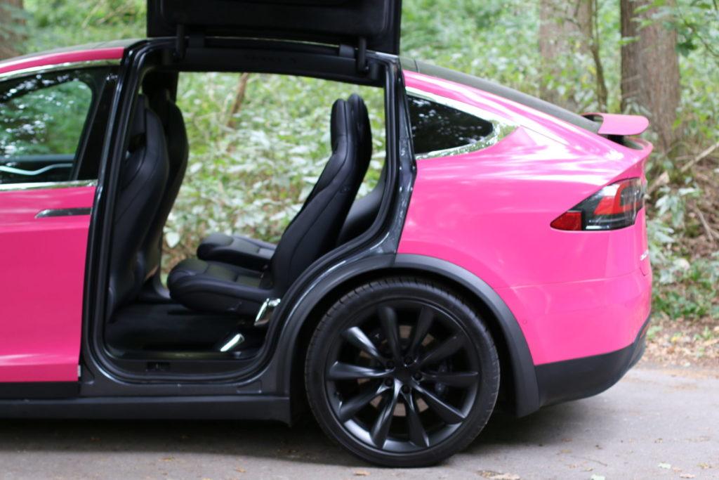 Tesla Model X90D Seitenansicht 6 Sitze dritte Sitzreihe falcon wings geöffnet parkend pink magenta Folierung Wrap Decal greenspeed emobility Aachen Deutschland NRW Gebrauchtwagen Gebrauchtfahrzeug kaufen